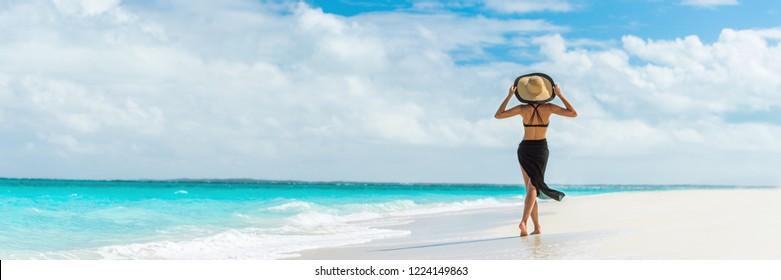 Роскошные путешествия летний пляж отдыха женщина ходьба в черной пляжной одежде юбка и шляпа на райском белом песке Карибский пляж. Леди турист на карибском курорте отдыха. Баннер панорама пейзаж.