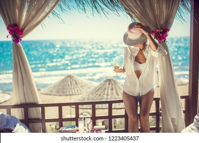 Luxury travel. Summer holiday girl enjoying vacation with champagne.