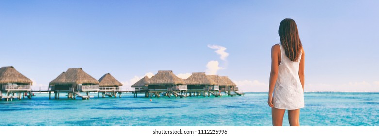 Luxury travel Tahiti vacation tourist woman at overwater bungalows famous resort in French Polynesia. Girl at tropical holiday destination panoramic banner landscape background.