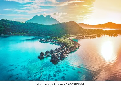 Luxury travel vacation aerial of overwater bungalows resort in coral reef lagoon ocean by beach. View from above at sunset of paradise getaway Bora Bora, French Polynesia, Tahiti, South Pacific Ocean