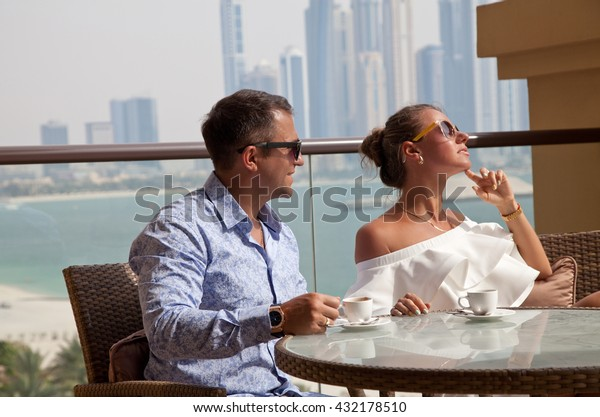 Luxury travel vacation couple relaxing with cup of coffee looking at view on Dubai famous travel destination. Amazing view of sea and city. (focus on man)