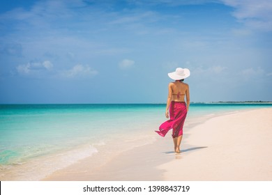 Luxury travel vacation elegant lady walking on beach in pink fashion skirt wrap relaxing on Caribbean holidays during winter.
