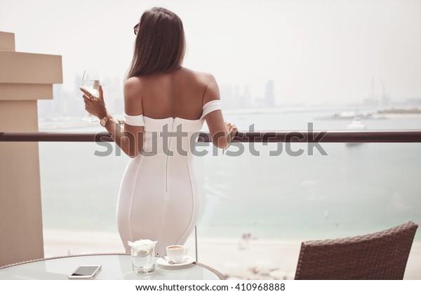 有名なドバイの旅行先で見えるシャンパングラスを持つ高級旅行バケーションの女性。セクシーなドレスを着た優雅な若い女性が休暇中に。旅のコンセプト。(ソフトフォーカス)