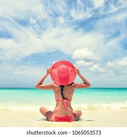 Luxury travel woman relaxing tanning with pink sun hat and bikini sitting on white sand Caribbean beach. Girl tourist on summer holiday at vacation resort. Tropical landscape square for social media.
