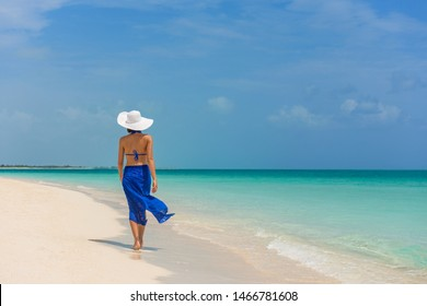 Luxury travel woman walking on perfect beach vacation Caribbean destination in blue dress skirt sarong. Elegant lady tourist relaxing on summer vacations wearing sun hat.