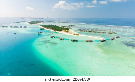 Luxury tropical resort and water villas in blue sea over coral reef from aerial view.