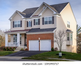 Luxury upscale American single family estate home with vinyl siding, double car garage door, covered porch, bay window, double gable roof in the USA