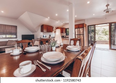 Luxury urban condominium or penthouse kitchen room interior with wooden table and white plate a patio overlooking jungle