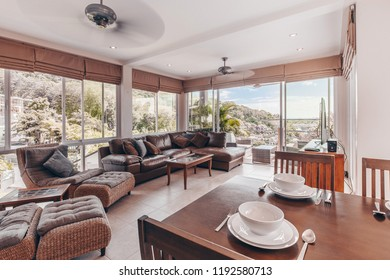 Luxury urban condominium or penthouse living room interior with huge view windows with a patio overlooking the city and jungle