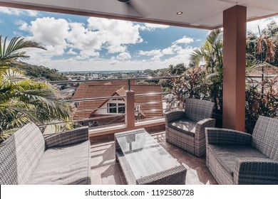 Luxury urban condominium or penthouse living room interior with a modular white suite and huge view windows with a patio overlooking the city,