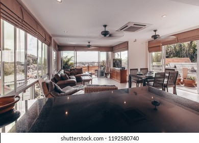 Luxury urban condominium or penthouse living room interior with huge view windows and a patio over looking the jungle and city