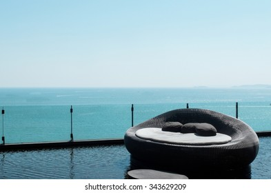 Luxury Used Sofa Bed with Soft Pillow as Interior Furniture with Blue Sea and Clear Sky as Copyspace at The Luxury Hotel Lounge on The Outdoor Balcony for Outside Meeting Party with Scenery Background