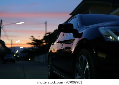 luxury vehicle black car travel road trips at night city with blur beautiful twilight dramatic sky, image selective focus on side mirror