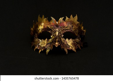 luxury, Venetian mask in gold and red with metallic pieces in the form of leaves. original and unique design, handmade crafts