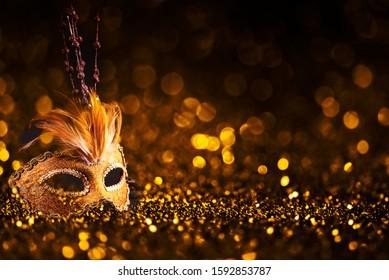 Luxury venetian mask on dark godlen bokeh background. New year and christmas party celebration design banner. Carnival masquerade fantasy costume ball.