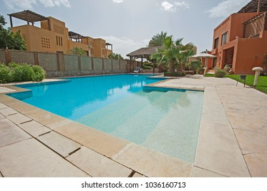 Luxury villa show home exterior at tropical summer holiday resort with swimming pool and garden