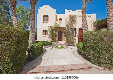 Luxury villa show home exterior view in a tropical resort with private garden and palm trees
