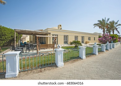 Luxury villa show home exterior view in a tropical resort with patio seating area and garden