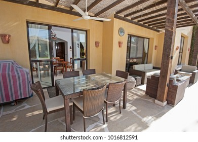 Luxury villa show home in tropical summer holiday resort with patio area showing sofa and dining table with chairs