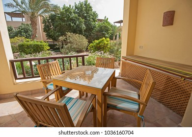 Luxury villa show home at tropical summer holiday resort with terrace patio in garden and table chairs