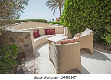 Luxury villa show home in tropical summer holiday resort with patio garden seating area showing sofa and table