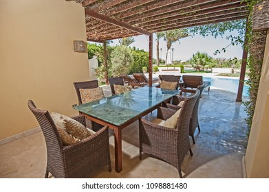Luxury villa show home in tropical summer holiday resort with swimming pool and outdoor dining table area