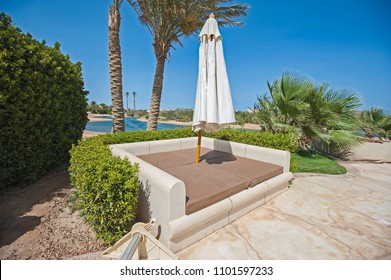 Luxury villa show home in tropical summer holiday resort with patio garden seating area showing sofa and umbrella