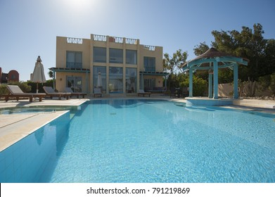 Luxury villa show home in tropical summer holiday resort with swimming pool and sun chairs