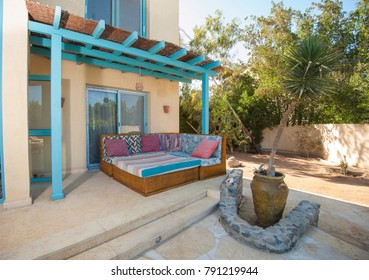 Luxury villa show home in tropical summer holiday resort with patio area showing sofa