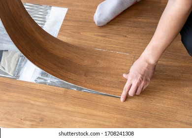 Luxury vinyl floor tiles collection : laying wooden vinyl tile sheet to install on glue cement surface at interior renovation site