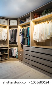 Luxury walk in closet / dressing room with lighting and jewel display. Dresses, handbags, blouses and sweaters on hangers in the wardrobe. Vertical.