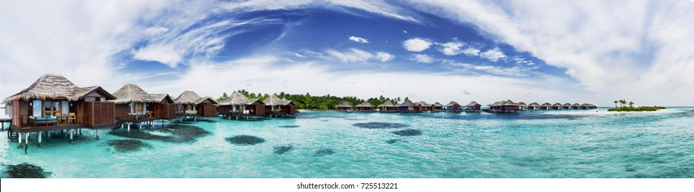 Luxury water villa panorama with clear ocean on sunny day, Maldives