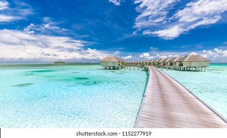 Luxury water villas in Maldives islands, long wooden jetty or pier into blue tropical sea, lagoon. Blue sky, sunny day in Maldives resort. Summer holiday and vacation concept, travel destination idea