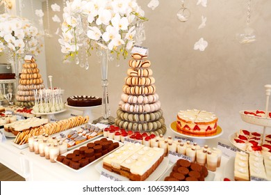 luxury wedding catering, table with modern desserts, cupcakes, sweets with fruits. delicious candy bar at expensive wedding reception.