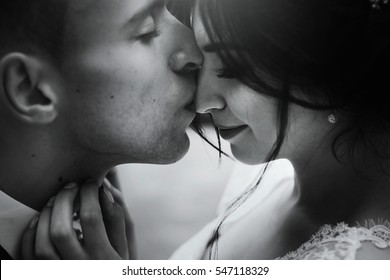 luxury wedding couple embracing hugging and kissing in sunny light. gorgeous bride and stylish groom in sensual tender emotional moment. black white photo. portraits