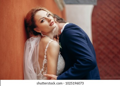 luxury wedding couple hugging at old building wall. stylish bride and groom embracing and kissing in city street.  romantic sensual moment. man kissing woman in white dress