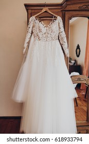 luxury wedding dress on hanger at wooden closet in rustic room. space for text. wedding morning preparation,getting ready. stylish gown