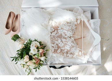 Luxury wedding dress in white box, beige women's shoes and bridal bouquet on bed, copy space. Bridal morning preparations. Wedding concept - Shutterstock ID 1538144603