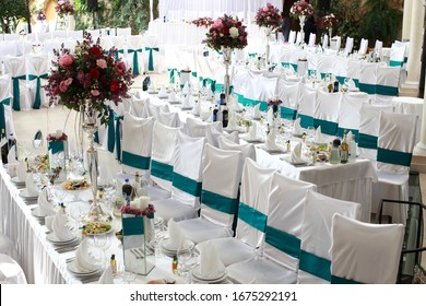 Luxury wedding reception dinning table setup with eucalyptus branches and gold geometric decoration on a rustic wooden table
