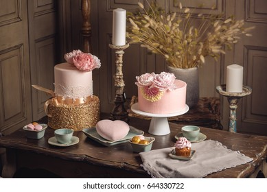 Luxury wedding table with a beautiful pink cake decorated with mastic and rose gold in antique classic expensive interior. the concept of chic wedding desserts
