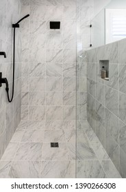 Luxury wheelchair accessible shower with marble floor and walls.