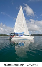 Luxury white catamaran boat in the bay with reflexion in the sea