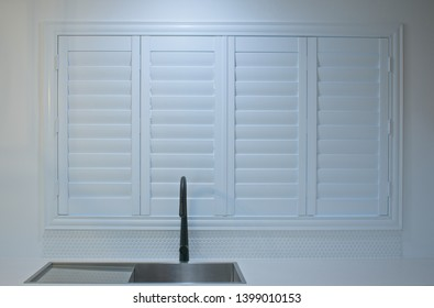 Luxury white indoor plantation shutters in a modern kitchen, closed shutters.