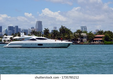 Luxury white motor yacht idling off luxury Miami Beach island homes on the Florida Intra-Coastal Waterway with Miami tall building skyline in the background.