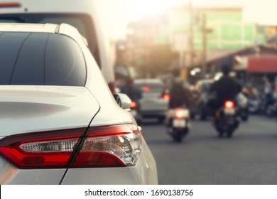 Luxury of whtie car stop beside road. with blurred background evironmnet of transportation in the city.