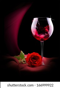 luxury wine glass with red silk and rose on a black background