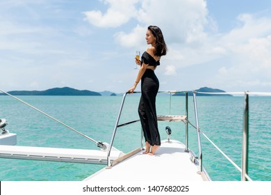 Luxury woman in evening black dress drinking champagne on the deck of a boat