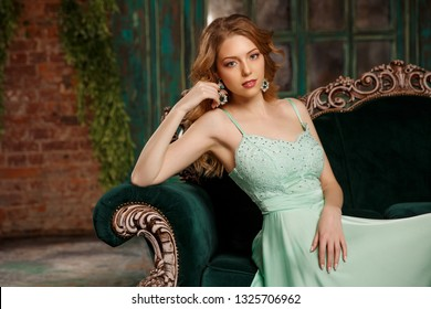 Luxury woman model in a mint-colored dress sitting on a vintage couch. Beauty girl with a stunning makeup and hairstyle.