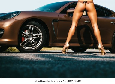 Luxury woman. Sport car and luxurious butt woman. Sexy ass near golden brown sports car on luxury background. Luxury buttoks