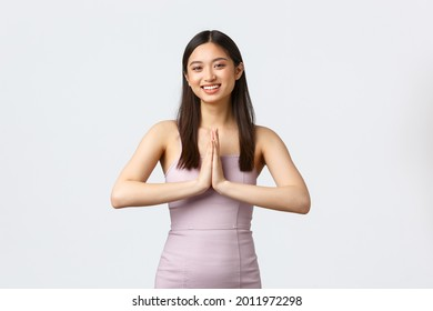 Luxury women, party and holidays concept. Charming asian woman in evening dress, hold hands in plead or namaste sign, greeting guests at celebration, smiling friendly, white background